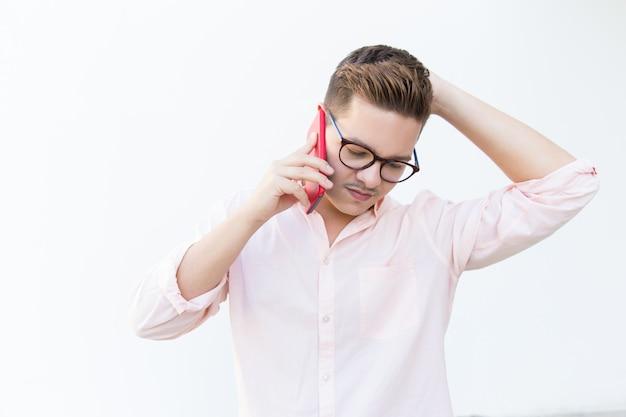 Ragazzo concentrato pensieroso in occhiali grattandosi la testa