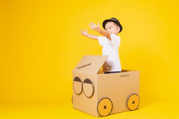 Ragazzo dei piccoli bambini che guida l'automobile del cartone