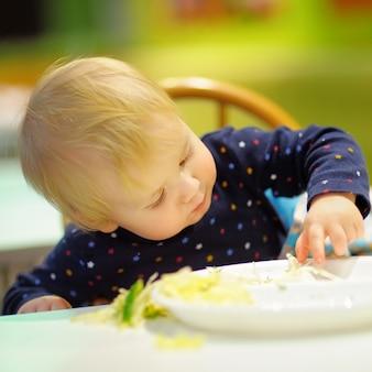 Ragazzo del bambino che gioca con il cibo al caffè al chiuso