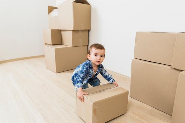 Ragazzo del bambino che gioca con la scatola di cartone commovente a nuova casa
