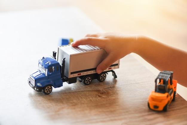 Ragazzo del bambino che gioca i giocattoli sulla tabella a casa - mani del bambino che giocano camion di auto giocattolo