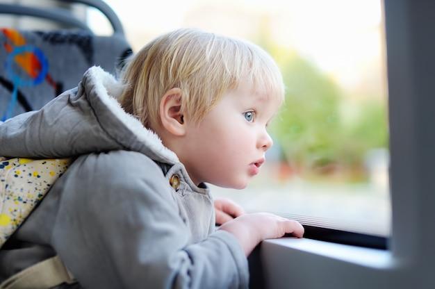 Ragazzo del bambino che osserva fuori finestra del tram o del treno