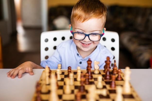 Ragazzo del bambino con sindrome di down con grandi occhiali blu che giocano a scacchi nella scuola materna