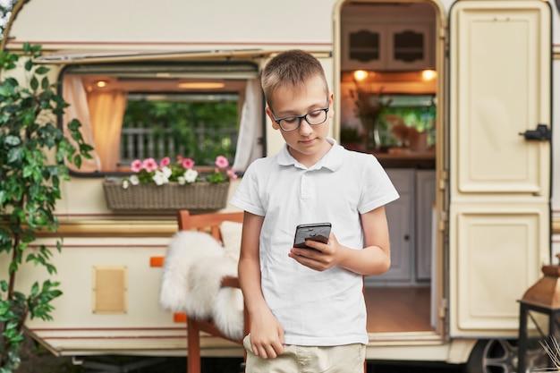 Ragazzo del bambino con un telefono in vacanza in estate vicino alla casa su ruote