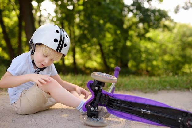 Ragazzo del bambino in casco di sicurezza che impara a guidare scooter