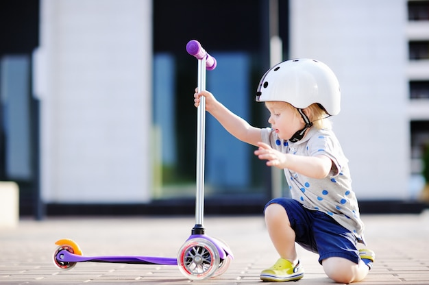 Ragazzo del bambino in casco di sicurezza imparando a guidare scooter