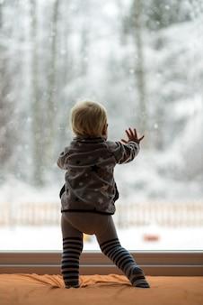 Ragazzo del bambino in piedi contro una finestra che guarda fuori