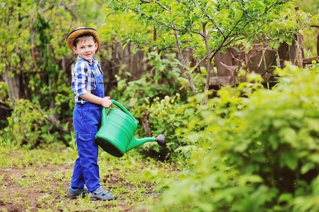 Ragazzo del bambino in un cappello di paglia e un giardiniere tuta blu che innaffia fiori e giovani alberi