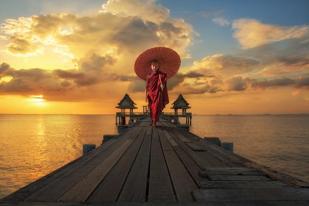 Ragazzo del debuttante che cammina sul ponte boscoso con l'ombrello rosso