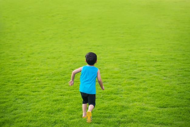 Ragazzo del piccolo bambino che corre in avanti nel grande giorno di estate del campo di erba verde.