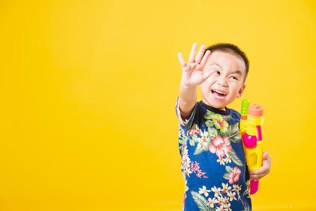 Ragazzo del piccolo bambino così felice nel giorno di festival di songkran che tiene pistola ad acqua sulla parete gialla