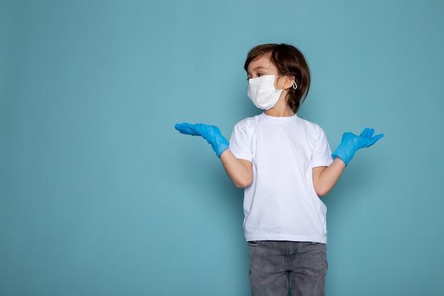 Ragazzo del piccolo bambino nella maschera protettiva sterile bianca e guanti blu sulla parete blu