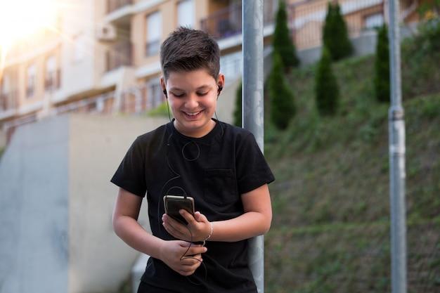 Ragazzo dell'adolescente in vestiti casuali che ascolta la musica sul suo telefono cellulare.