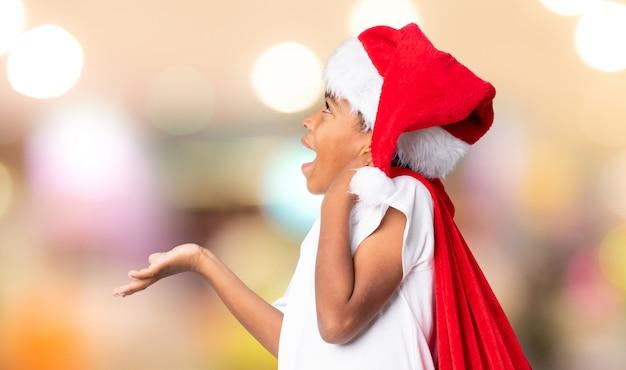 Ragazzo dell'afroamericano con il cappello di natale e prendere una borsa con i regali che fanno gesto di sorpresa sopra la parete vaga