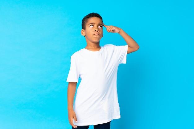 Ragazzo dell'afroamericano sopra l'azzurro isolato che ha dubbi e con l'espressione confusa del fronte