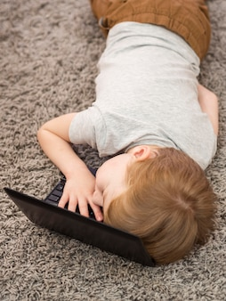 Ragazzo dell'angolo alto che pone con la sua testa su un computer portatile