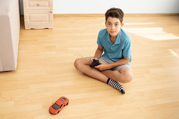 Ragazzo della foto a figura intera che gioca con un'automobile elettrica