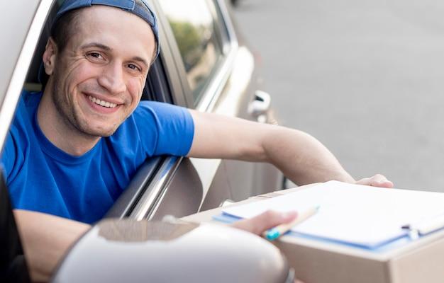 Ragazzo delle consegne di smiley in auto