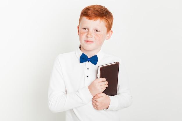 Ragazzo dello zenzero che tiene un libro