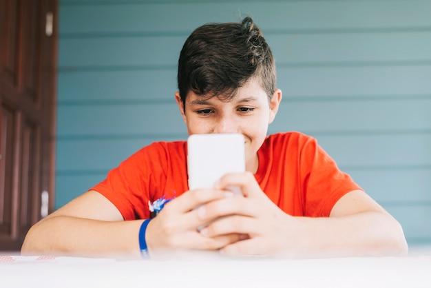 Ragazzo di 13 anni caucasico bello che porta maglietta rossa che si siede all'aperto facendo uso dell'aggeggio elettronico