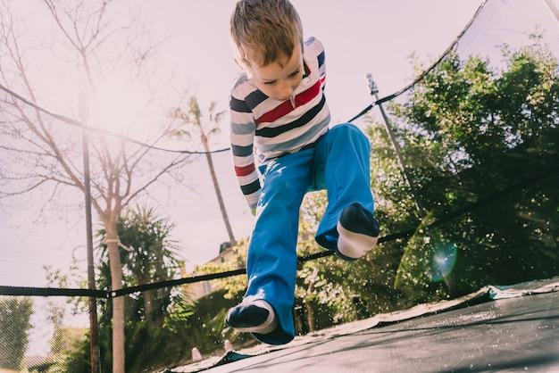 Ragazzo di 5 anni che salta su un trampolino godendo la sua energia, faccia con espressioni di felicità per giocare all'aperto.