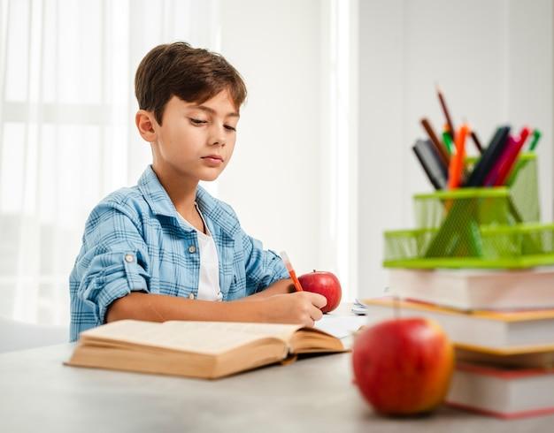 Ragazzo di angolo basso che mangia mela mentre studiando
