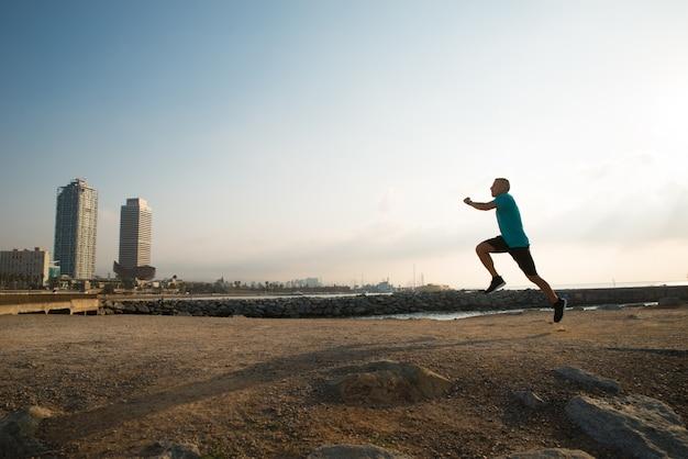Ragazzo di atletica città che corre in mattina