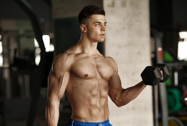Ragazzo di bodybuilder muscolare facendo esercizi con manubri in palestra