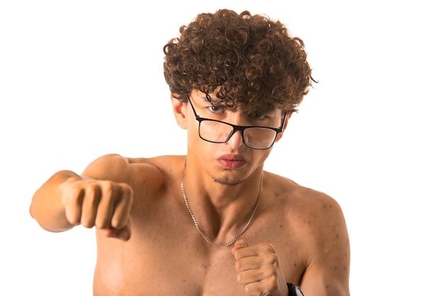 Ragazzo di capelli ricci in occhiali optique punzonatura con la mano destra su sfondo bianco