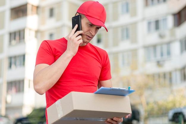 Ragazzo di consegna basso angolo con telefono