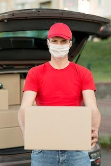 Ragazzo di consegna che indossa una maschera colpo medio