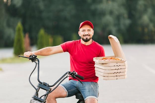 Ragazzo di consegna di smiley del colpo medio sulla motocicletta
