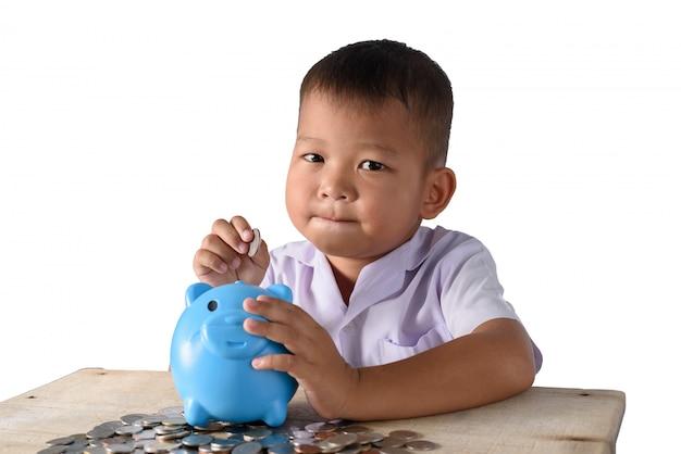 Ragazzo di paese asiatico sveglio che mette le monete nel porcellino salvadanaio isolato su fondo bianco