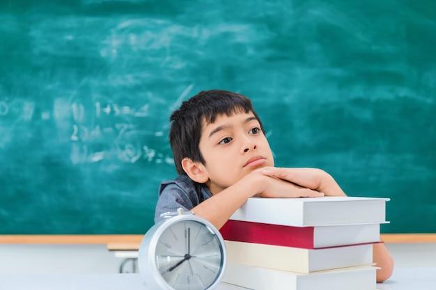 Ragazzo di scuola asiatico che pensa e che sogna con il libro e la sveglia sulla tavola