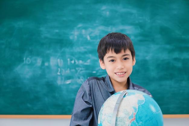 Ragazzo di scuola asiatico che sorride e che pensa con il globo sulla lavagna