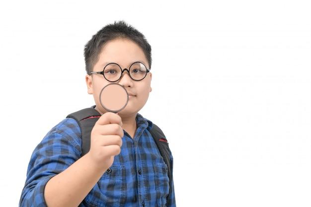Ragazzo di scuola che indossa le lenti e che tiene una lente d'ingrandimento