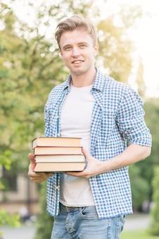 Ragazzo di scuola con il libro nel parco