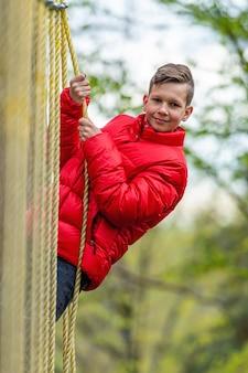 Ragazzo di scuola dell'adolescente che gode dell'attività in un parco avventura di arrampicata in una giornata di primavera
