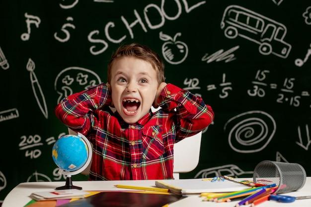 Ragazzo di scuola emotivo seduto sulla scrivania con molti rifornimenti di scuola. primo giorno di scuola. ragazzo del bambino della scuola elementare. di nuovo a scuola. bambino della scuola elementare.