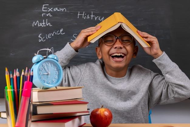 Ragazzo di scuola premuroso allegro con i rifornimenti della cancelleria sullo scrittorio dell'aula