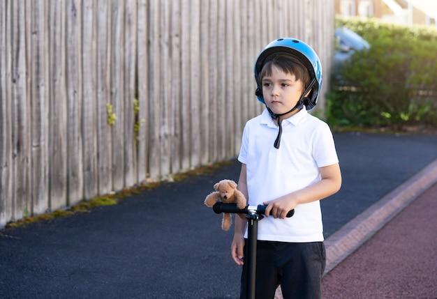 Ragazzo di scuola ritratto cavalcare uno scooter a scuola, bambino che indossa un casco di sicurezza in sella a un rullo, bambino in piedi con orsacchiotto guardando in profondità, tempo libero attivo e sport all'aperto per bambini.
