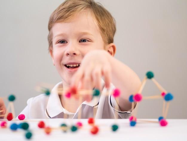 Ragazzo di smiley che gioca con il gioco di atomi colorati