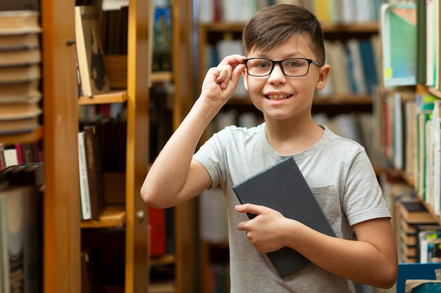 Ragazzo di smiley con gli occhiali in biblioteca