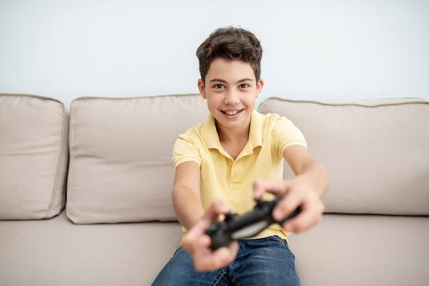 Ragazzo di smiley di vista frontale che gioca con il controller