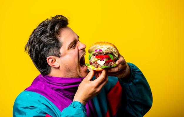 Ragazzo di stile in abiti anni '80 con grande hamburger su spazio giallo