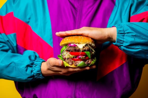 Ragazzo di stile in abiti anni '80 con grande hamburger