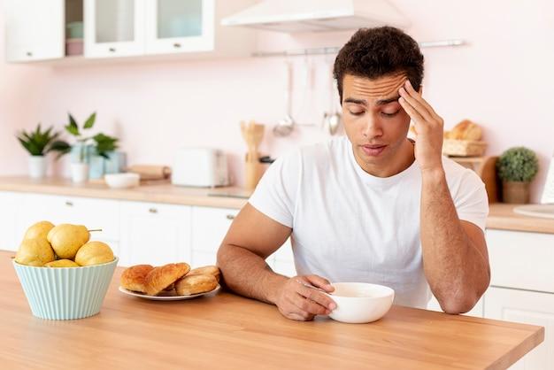 Ragazzo di tiro medio con ciotola di cereali in cucina