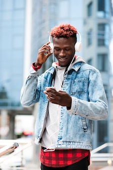 Ragazzo di tiro medio con cuffie guardando il telefono