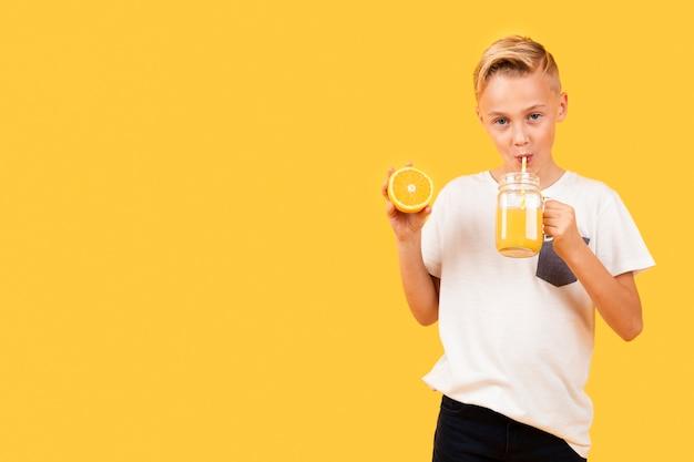 Ragazzo di vista frontale che beve il succo di arancia