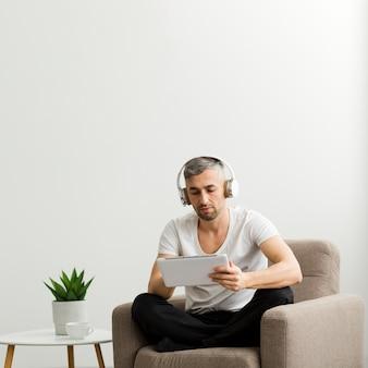 Ragazzo di vista frontale con le cuffie guardando il suo tablet